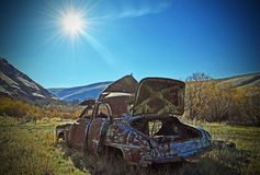 Bullet Riddled Abandoned Car, In Rock Creek. This is bullet riddled Car is one of several old cares in a area could Rock Creek in south west Washington Royalty Free Stock Images