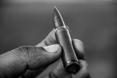 Bullet. A rifle bullet held in hand of a soldier Stock Photo