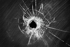 Bullet shot cracked hole on broken window glass Royalty Free Stock Images