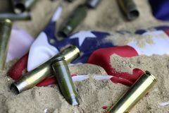 Bullet and usa flag in the sand war. Many shell casings from bullets of different caliber in the background chaos concept in the world Stock Photos