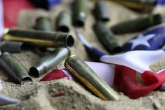 Bullet and usa flag in the sand war. Many shell casings from bullets of different caliber in the background chaos concept in the world Stock Image