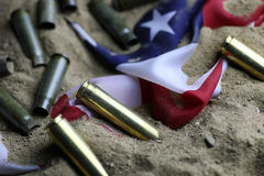 Bullet and usa flag in the sand war. Many shell casings from bullets of different caliber in the background chaos concept in the world Royalty Free Stock Photo