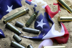 Bullet and usa flag in the sand war. Many shell casings from bullets of different caliber in the background chaos concept in the world Royalty Free Stock Image