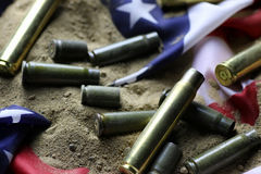 Bullet and usa flag in the sand war. Many shell casings from bullets of different caliber in the background chaos concept in the world Stock Photography
