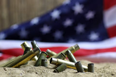 Bullet and usa flag in the sand war. Many shell casings from bullets of different caliber in the background chaos concept in the world Royalty Free Stock Images