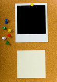 Bulletin board. With blank polaroid photograph and a yellow sticky or post-it note and extra push pins Stock Images