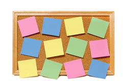 Bulletin Board With Blank Notes. Cork bulletin board full of blank sticky notes ready for you to add your own message, notes or more.  Isolated on a white Royalty Free Stock Photos