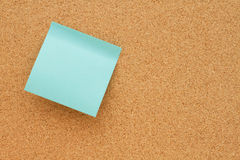 Bulletin board with a blank teal sticky note Royalty Free Stock Photo