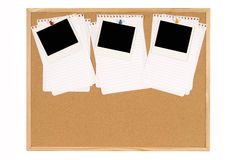 Row of three Polaroid photo prints on a cork notice board pinned to untidy torn notepaper, copy space Stock Image