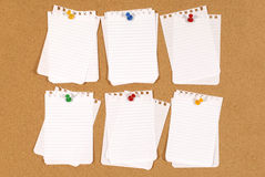 Cork bulletin or notice board with pinned untidy torn notepaper, copy space Stock Image