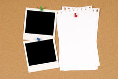 Two polaroid photo frames pinned to a cork board background with blank torn notepaper, copy space Royalty Free Stock Photo