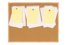 Cork bulletin board with untidy torn notepaper and yellow post-it style sticky notes Stock Photos
