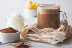 BULLETPROOF CACAO. Ketogenic keto diet hot drink. Cacao blended with coconut oil and butter. Cup of bulletproof cacao. And ingredients on white background royalty free stock photos