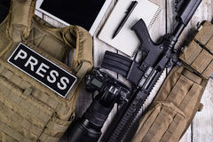 Bulletproof vest,camera,rifle,notebook,army belt and tablet touc Stock Photos