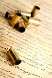 Bullets. Spent bullet cases, macro with focus on foremost shell, on bill of rights Royalty Free Stock Photo