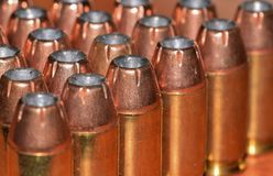 Bullets arranged in rows. Close up of .45 caliber brass hollow point bullets standing up on end, arranged in an angled formation Royalty Free Stock Photography