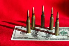 Bullets and banknotes on a black background as an abstract example of the causes of military conflicts in the world stock photo