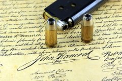 Bullets on Bill of Rights - The Right to Bear Arms. Ammunition on US Constitution John Hancock's signature Royalty Free Stock Photography