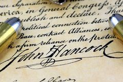 Bullets on Bill of Rights - The Right to Bear Arms. Ammunition on US Constitution John Hancock's signature Stock Images