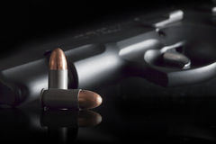 Bullets and CZ 75 Handgun. Two copper topped bullets, one standing on end and one laying on side with barrel and trigger of CZ 75 9mm handgun blurred in black Royalty Free Stock Photography