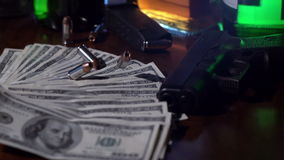 Bullets fall onto pile of money in slow motion stock video