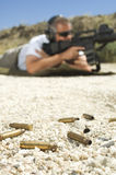 Bullets On Ground With Man Aiming Machine Gun Royalty Free Stock Images