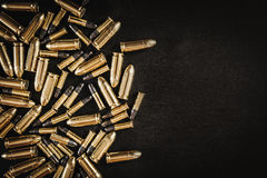 Bullets from the gun on the table. Bullets from the gun placed on a black wooden table Royalty Free Stock Image