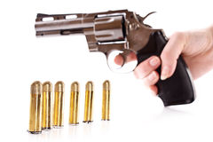 Bullets and revolver in hand. Royalty Free Stock Images
