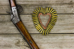 Bullets in the shape of heart next to rifle on rustic wooden background Stock Images