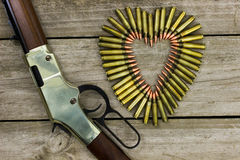 Bullets in the shape of heart next to rifle on rustic wooden background Royalty Free Stock Photo