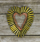 Bullets in the shape of heart on rustic wooden background Stock Photos