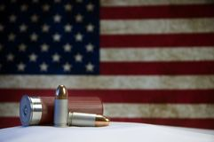 Bullets and US Flag. 9mm bullets, a shotgun shell and US flag Stock Image