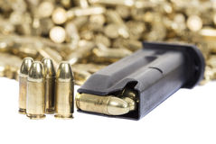 Bullets on white. A loaded gun clip with a pile of bullets in the background Stock Image