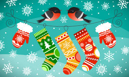Bullfinches on the line with Christmas gloves and socks. Snowflakes and snowy hills background. Royalty Free Stock Photography