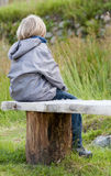 Bullied. A young and sad young boy sits alone on a park bench Stock Image