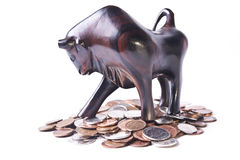 Bullish Market. A strong, triumphant bull atop a pile of coins, signifying an optimistic or bullish foreign currency (forex) market Stock Photos