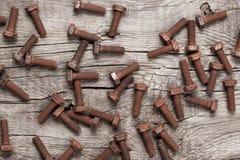Bullone di vite arrugginito sulla tavola di legno fotografie stock