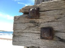 Bulloni del ferro battuto sul fascio di legno stagionato Immagine Stock Libera da Diritti
