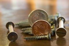 Bulloni di viti e centesimo due per simbolizzare le professioni ed i profitti immagine stock