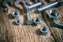 Bulloni e dadi delle chiavi su fondo di legno Fotografia Stock