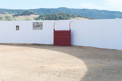 Bullring. Part of a bullring with white wall and red defenses, the background shows the mountains Stock Photography