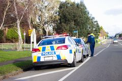 A Police officer pulls over a speeding driver on the main road of Bulls in New Zealand. Bulls, New Zealand - 2 July 2016: A Police officer pulls over a speeding Royalty Free Stock Photo