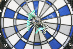 Bullseye em uma parede com alguns dardos imagens de stock