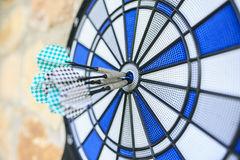 Bullseye on a wall with some darts Royalty Free Stock Images