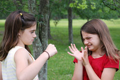 Bully. Older schoolgirl bullying a younger girl in the park Stock Images