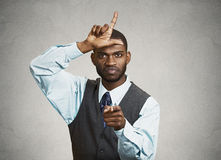 Bully boss executive man. Closeup portrait angry mad young Unhappy Man, student displaying Loser Sign on forehead, pointing at you with disgust, isolated grey Stock Photos