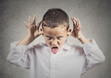 Bully child. Closeup portrait angry young Unhappy boy, young student Mocking teasing, taunting other children isolated grey wall background. Negative human royalty free stock photo