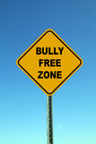 Bully Free Zone. Yellow bully free school zone road sign against a beautiful blue sky Royalty Free Stock Image