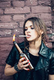 Bully girl lighting up a cigarette from Molotov cocktail bomb in her hand Stock Photography