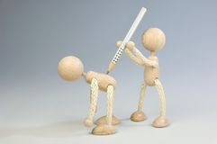 Bullying. A wooden doll attacks another one with a pencil Stock Photos